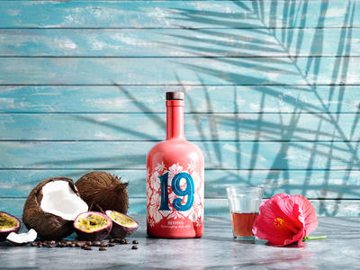 A bottle of Blossa 19 Aloha, a glögg glass, passion fruit, hibiscus flower, coconut and coffee beans