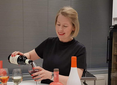 A woman pouring some glögg into a glass. Glögg bottles on a table.