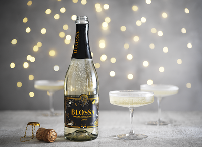 Bottle of Blossa Sparkling & Spices and three champagne glasses