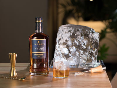 Bottle of Larsen Cognac VSPO with a glass of drink and a big ice rock